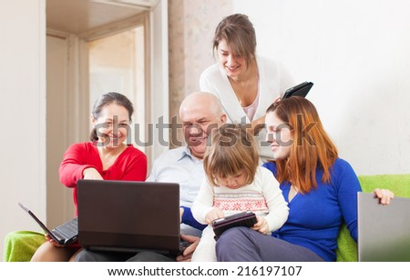 family enjoys on sofa in livingroom room with few laptops at home - stock photo