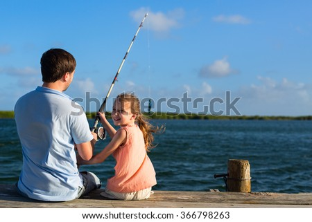 Family father and daughter fishing together from wooden jetty - stock photo