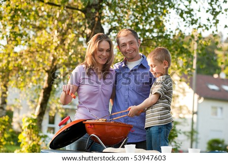 Family - father and son - having a barbecue party, the child is very concentrated on doing the cooking work - stock photo