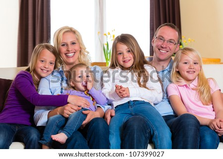 Family, father, mother and four sisters sitting on a couch in their living room - stock photo