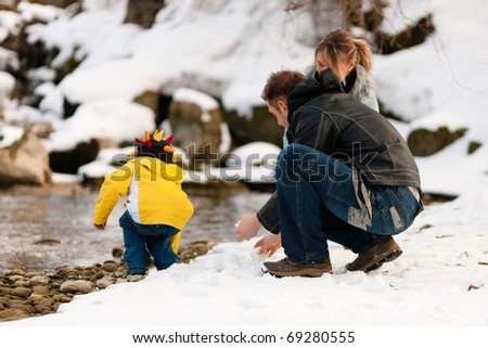 Family - father, mother and son to be seen - on a walk along a riverbank in winter; they are making snowballs - stock photo
