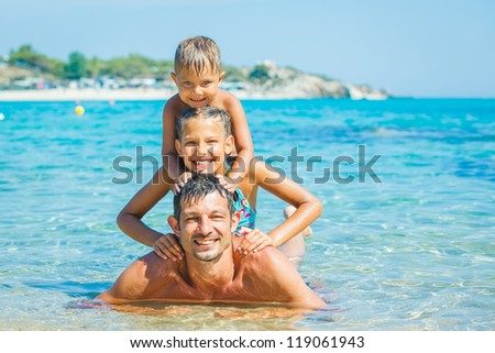 Family - father with his kids have fun and swimming in the transparent sea - stock photo