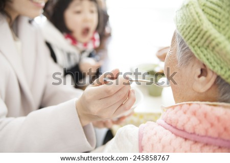 family feeding an old lady - stock photo