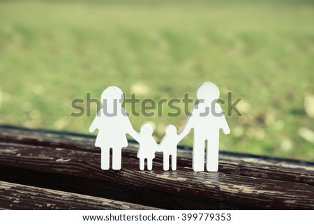 Family figures on a bench in park - stock photo