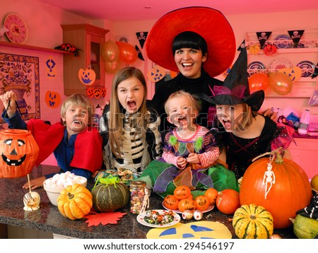 Family/friends posing for the camera in their halloween costumes. They are standing in the kitchen with party food and treats set out in front of them.  - stock photo