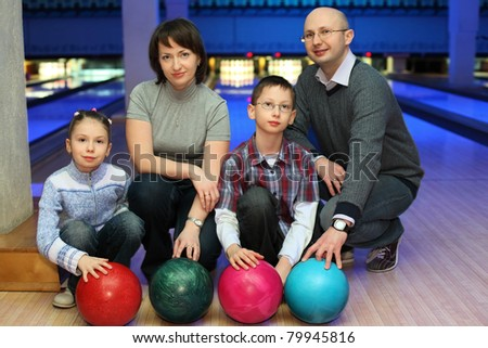 Family from four persons  of squatting in club for bowling and holds on to balls, focus on children and balls - stock photo