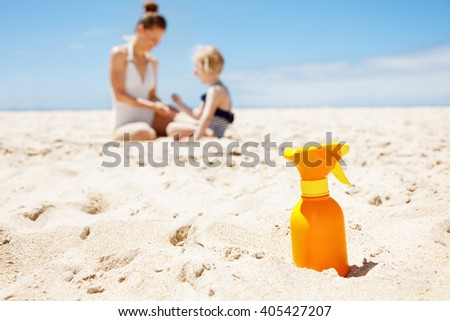 Family fun on white sand. Closeup on sunscreen bottle at sandy beach on a sunny day. Mother and child in swimsuits playing in background - stock photo