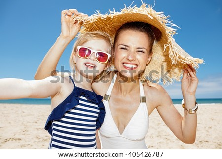 Family fun on white sand. Happy mother and daughter under big straw hat taking selfie at sandy beach on a sunny day - stock photo