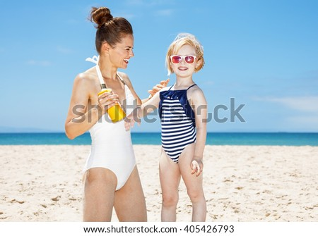 Family fun on white sand. Happy mother applying sunscreen on child's arm at sandy beach on a sunny day - stock photo