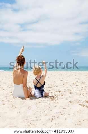Family fun on white sand. Seen from behind mother and child in swimsuits sitting at sandy beach on a sunny day and pointing up on something - stock photo