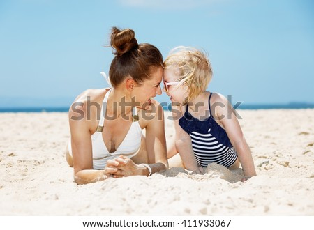 Family fun on white sand. Smiling mother and child in swimsuits playing while laying on sandy beach on a sunny day - stock photo