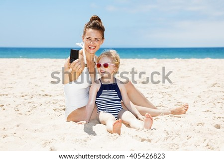 Family fun on white sand. Smiling mother and daughter in swimsuits taking selfies with digital camera at sandy beach on a sunny day - stock photo