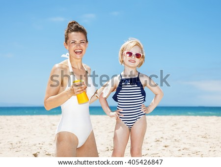 Family fun on white sand. Smiling mother applying sunscreen on daughter's arm at sandy beach on a sunny day - stock photo