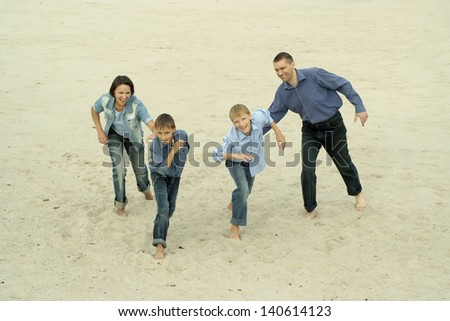 Family fun running barefoot in the sand - stock photo
