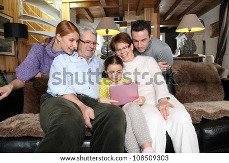 family gathering at home with laptop - stock photo