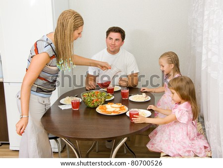 Family gathers for dinner at the table - stock photo