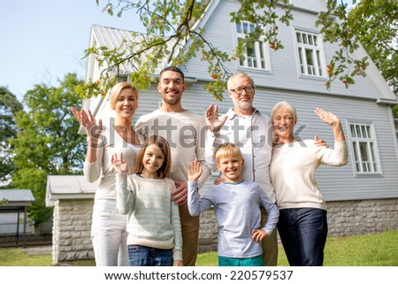 family, generation, gesture, home and people concept - happy family standing in front of house waving hands outdoors - stock photo