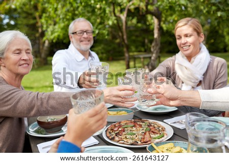 family, generation, home, holidays and people concept - happy family having dinner and clinking glasses in summer garden - stock photo