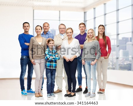 family, generation, real estate and people concept - group of smiling men, women and boy over empty apartment or office room background - stock photo