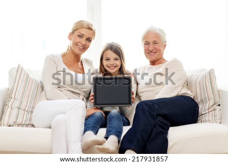 family, generation, technology and people concept - smiling mother, daughter and grandmother with tablet pc computer sitting on couch at home - stock photo