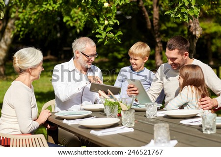 family, generation, technology, home and people concept - happy family with tablet pc computers sitting at table in summer garden - stock photo