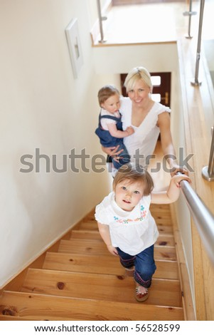 Family going upstairs looking in the camera - stock photo