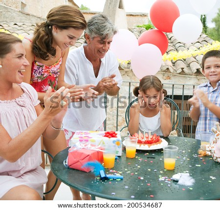Family group enjoying and celebrating a young girl child birthday during a summer day, sitting around a table with a birthday cake and gifts and a surprised birthday girl. Family celebrating outdoors. - stock photo