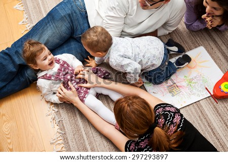 family group of five - two babies and three adults lying on the carpet, mom is tickling her daughter. - stock photo