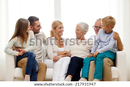 family, happiness, generation and people concept - happy family sitting on couch at home - stock photo