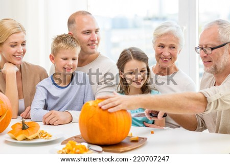family, happiness, generation, holidays and people concept - happy family making halloween pumpkins at home - stock photo