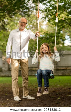 family, happiness, generation, home and people concept - happy grandfather and  granddaughter swinging on teeterboard outdoors - stock photo