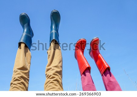 Family have fun wearing rain boots. Funny legs over blue sky in early spring, focus on mothers legs - stock photo