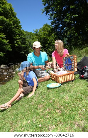 Family having a picnic by a river - stock photo