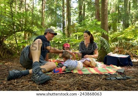 Family having a picnic outdoors in Redwoods Rotorua, New Zealand. - stock photo