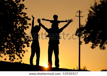 Family having a walk at sunset, the child sitting on his father's shoulders waving at the viewer; the whole scene is shot back lit, very tranquil and peaceful - stock photo