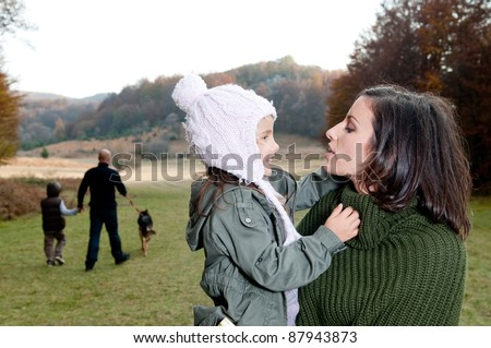 Family having a walk outdoors in autumn - stock photo