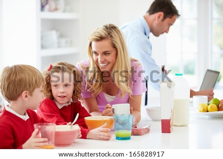 Family Having Breakfast In Kitchen Before School And Work - stock photo