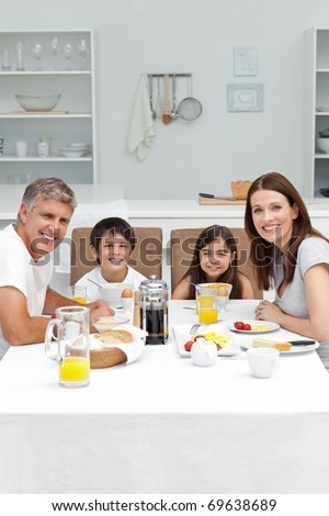 Family having breakfast in the kitchen at home - stock photo