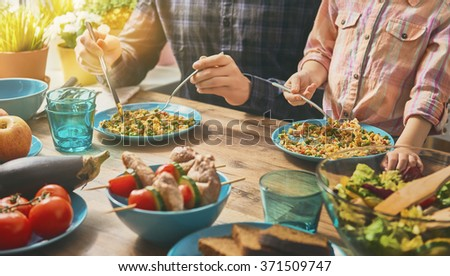 Family having dinner together sitting at the rustic wooden table. Enjoying  family dinner together. - stock photo