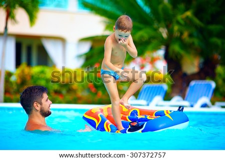 family having fun in swimming pool, summer vacation - stock photo