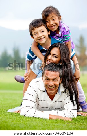 Family having fun lying on top of each other outdoors - stock photo