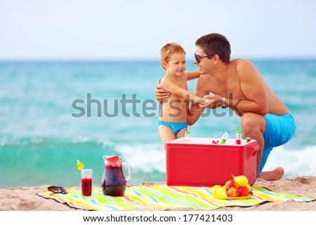 family having fun on beach picnic - stock photo