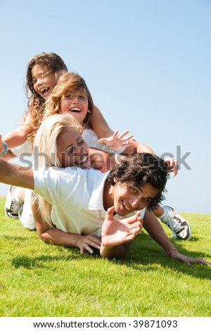 Family having fun on meadow - stock photo