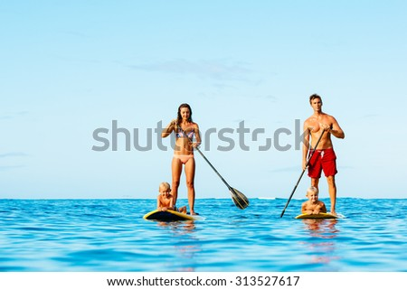 Family Having Fun Stand Up Paddling Together in the Ocean on Beautiful Sunny Morning - stock photo
