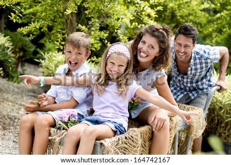 family having fun with a barrow in a greenhouse - stock photo