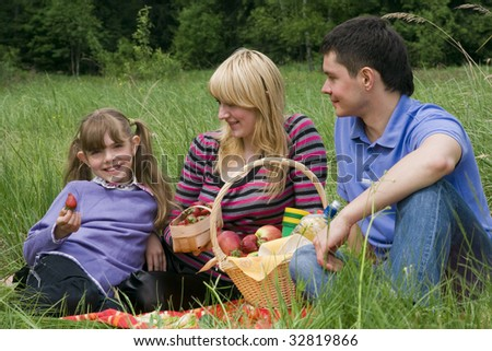 Family having picnic in park. Parents and child on picnic in the forest. Mother, father and daughter relaxing. Girl is holding strawberry. - stock photo