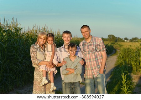 Family having rest in field at sunset - stock photo