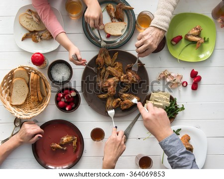family having roasted chicken wings for dinner top view - stock photo