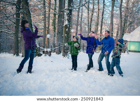 Family having snowball fight in snow in winter background - stock photo