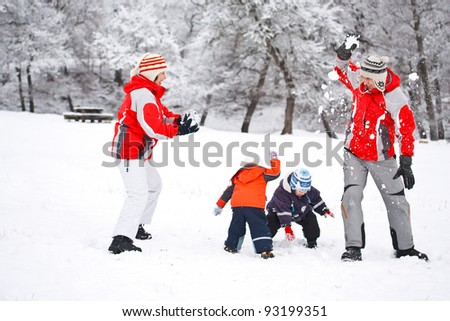 Family having snowball fight in snowy woodland - stock photo